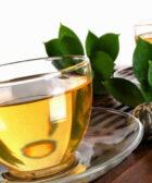 Te verde con taza transparrente encima de mesa de madera.